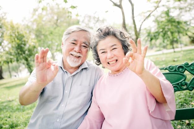 幸せなアジアの高齢者のカップルとok手のサイン