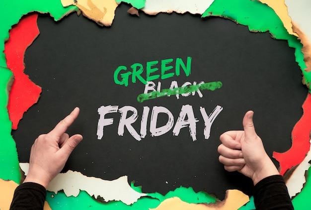 緑の金曜日、焼けた色紙で焼かれたフレーム。 okサインを示し、人差し指を指す手。テキスト「ブラックフライデーセール」、取り消し線または「ブラック」の取り消し線効果を「グリーン」に修正。
