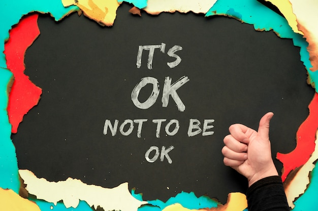 黒い壁の焼けた紙の枠に「大丈夫じゃなくても大丈夫」というテキストとokのサインが表示された手。人格障害および精神保健意識月間を患っている人のための肯定的な引用。