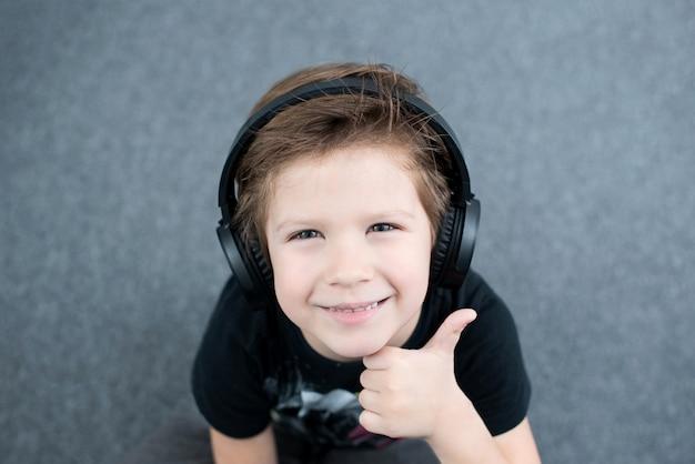 ヘッドフォンで少年はokサインを示しています