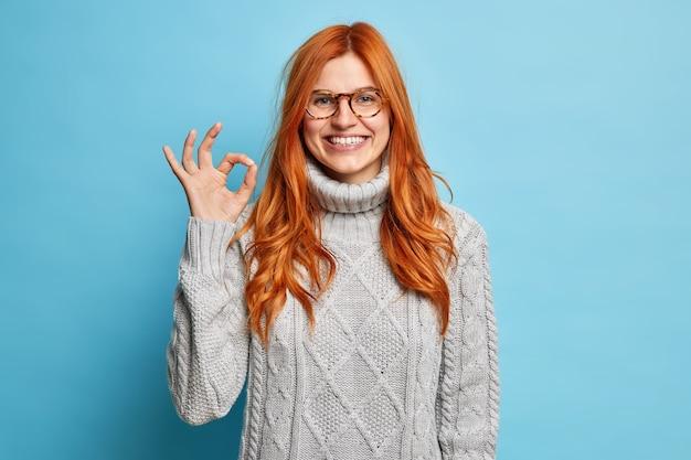Ладно ладно. улыбающаяся рыжая женщина делает отличный знак, полностью согласна с вашим предложением, одобряет что-то одетое в серый свитер.