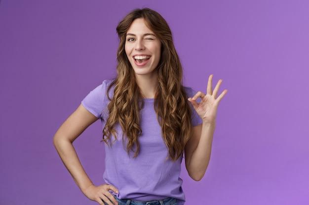 了解しました。生意気な軽薄なガールフレンドウィンクコケティッシュショー大丈夫大丈夫okサイン笑顔で広く安心友達の衣装素晴らしいエクスプレス承認同意する良いアイデアスタンド紫の背景満足