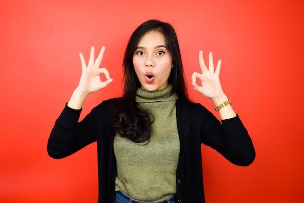 빨간색으로 격리된 검은색 스웨터를 사용하는 젊고 아름다운 아시아 여성의 확인 표시 또는 승인된 표시
