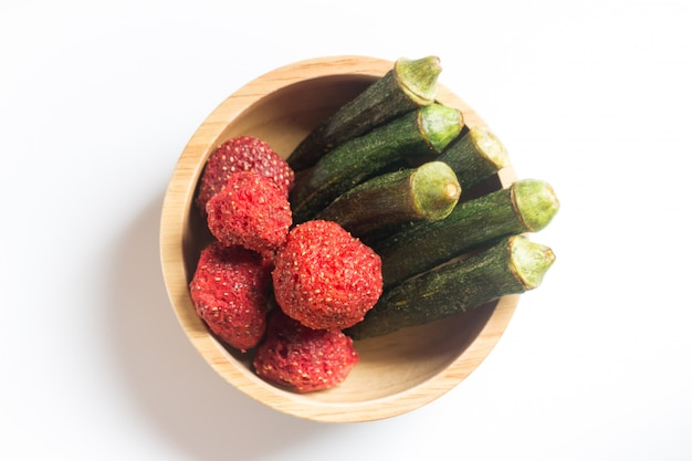 Okra chips and crispy strawberry in wooden bowl