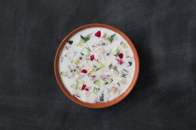 Okroshka. traditional russian summer yoghurt cold soup with vegetables on the black chalkboard
