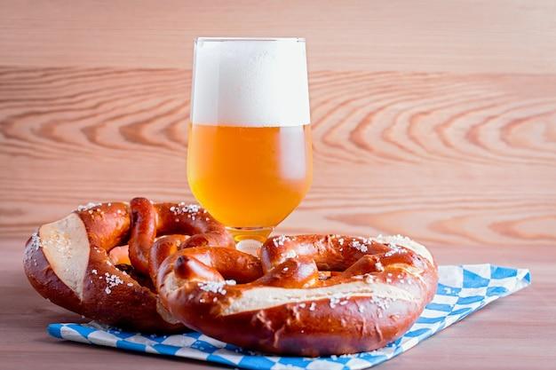 옥토버페스트 배경에는 맥주와 프레첼, 전통적인 바이에른 장식이 나무 탁자 위에 닫혀 있습니다.