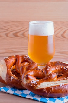 Oktoberfest background with beer and pretzels and traditional bavarian decor closeup on wooden table top