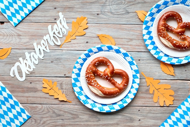 Oktoberfest banner with text space, hand holding pretzel and blue-white decorations