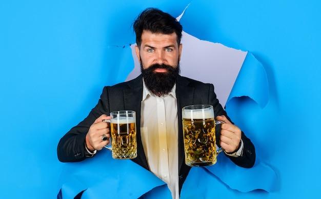 Октоберфест. бородатый мужчина с кружкой пива, глядя через отверстие для бумаги. напитки, алкоголь и люди концепции.