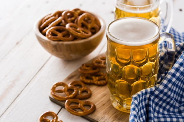 Oktoberfest beer and pretzel on white wooden table