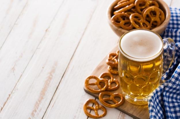 Oktoberfest beer and pretzel on white wooden table.