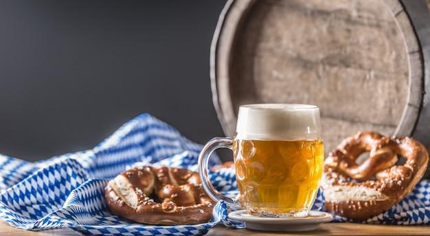 プレッツェルの木製バレルと青いテーブルクロスのオクトーバーフェストビール。