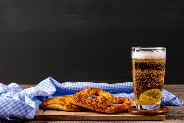 Oktoberfest beer with pretzel on wooden table with copyspce