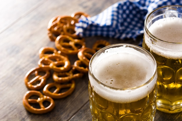 Oktoberfest beer with pretzels on wooden table copyspace