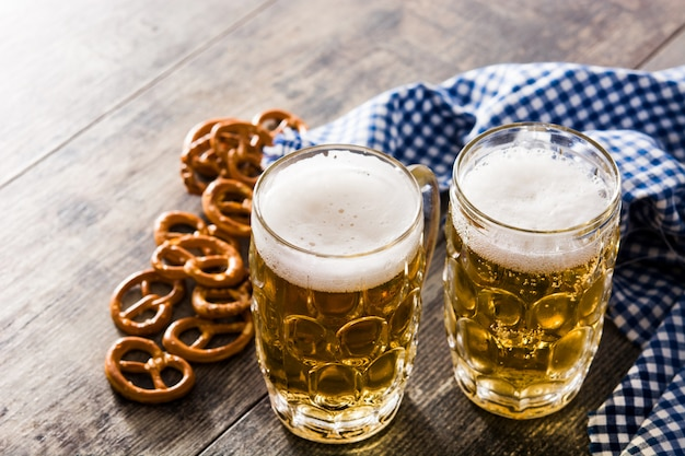 Oktoberfest beer with pretzels on wooden table