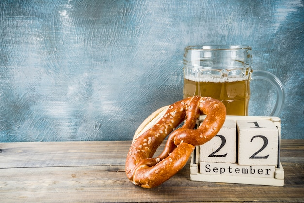 Oktoberfest celebration concept with beer glass mug, pretzel and old retro styled wooden calendar