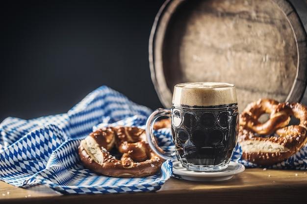プレッツェルの木製バレルと青いテーブルクロスが付いたオクトーバーフェストのダークビール。
