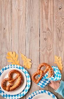 Oktoberfest, female hand in blue sweater holding pretzel, copy-space on wooden table