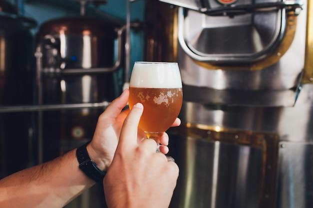 オクトーバーフェストフェスティバル。新鮮な醸造ビールの試飲。ブリューワーには、クラフトビールとグラスが入っています。醸造所のコンセプト。マグカップのビールを持つ男。アルコール。男性の醸造家はビールとグラスを保持しています。オクトーバーフェスト。バーマン。ブリューワー。