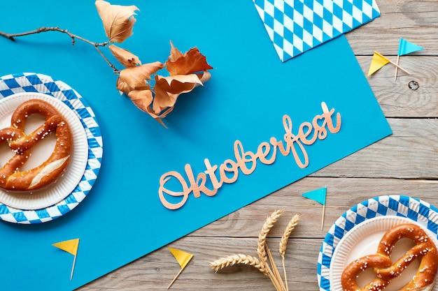 Октоберфест, квартира на деревенском деревянном столе с кренделями и осенними украшениями