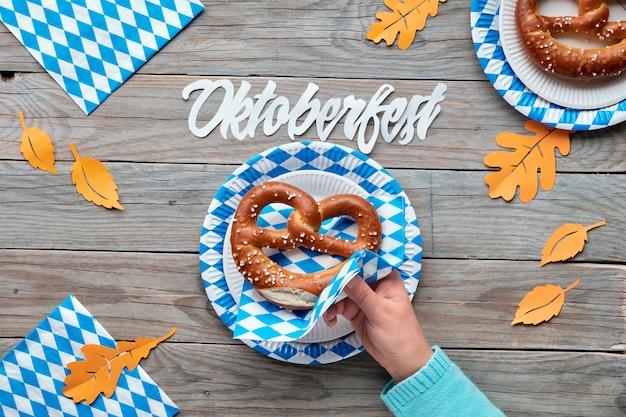 Октоберфест, плоская кладка на деревенском деревянном столе с кренделями на синих и белых клетчатых одноразовых бумажных тарелках и оранжевых осенних листьях