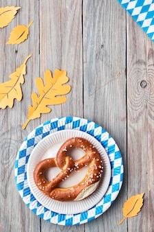 Oktoberfest, flat lay on rustic wooden table with pretzel and autumn decorations