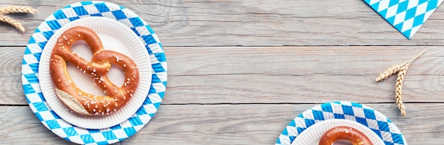 Oktoberfest, flat lay on rustic wooden table with pretzel and wheat ears, banner composition