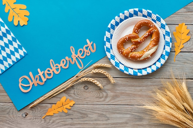 Oktoberfest, flat lay on rustic wooden table with pretzels and autumn decorations