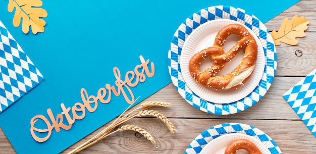 Oktoberfest, flat lay on wooden table covered with blue paper and pretzels on blue white paper plates