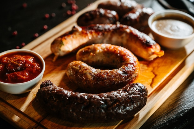 Oktoberfest food, appetizing meat sausages,. a large assortment on a wooden tray.