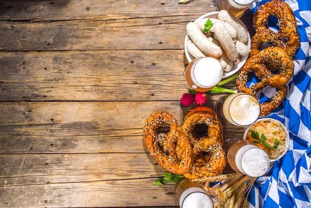 옥토버페스트 음식 배경, 전통 바이에른 휴일 음식 메뉴, 프레첼, 소금에 절인 양배추, 맥주 유리, 머그가 있는 소시지, 나무 태양 조명 배경 복사 공간 상단 보기 복사 공간