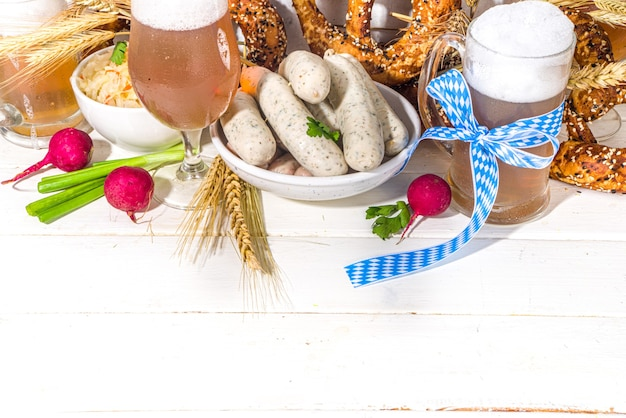 Oktoberfest food background, traditional bavarian holiday food menu, sausages with pretzels, sauerkraut, beer glass and mugs on white wooden sun lighted background copy space