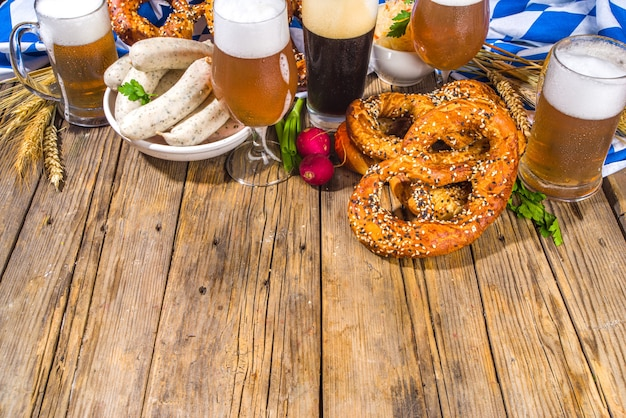 Oktoberfest food background, traditional bavarian holiday food menu, sausages with pretzels, sauerkraut, beer glass and mugs on wooden sun lighted background copy space top view copy space