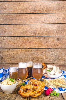 Oktoberfest food background, traditional bavarian holiday food menu, sausages with pretzels, sauerkraut, beer glass and mugs on wooden sun lighted background copy space
