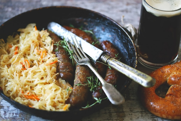 Пища октоберфест. горячие баварские колбаски с квашеной капустой в сковороде. вкусная пивная фестивальная еда