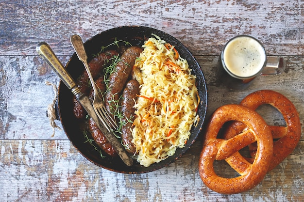 Oktoberfest food. hot bavarian sausages with sauerkraut in a pan. delicious beer festival food