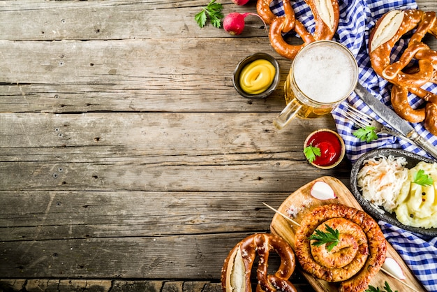 Oktoberfest food menu, bavarian sausages with pretzels, mashed potato, sauerkraut, beer bottle and mug old rustic wooden background, copy space above