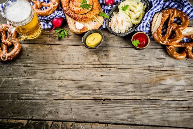 Oktoberfest food menu, bavarian sausages with pretzels, mashed potato, sauerkraut, beer bottle and mug old rustic wooden background
