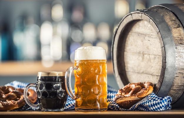 プレッツェルの木製樽と青いテーブルクロスが付いたオクトーバーフェストの大きくて濃いビール。