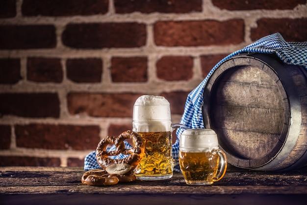 プレッツェルの木製樽と青いテーブルクロスを使ったオクトーバーフェストの大小のビール。