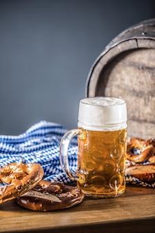 プレッツェルの木製樽と青いテーブルクロスが付いたオクトーバーフェストの大型ビール。