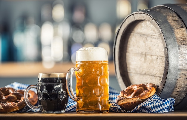 Oktoberfest large and dark beer with pretzel wooden barrel and blue tablecloth.