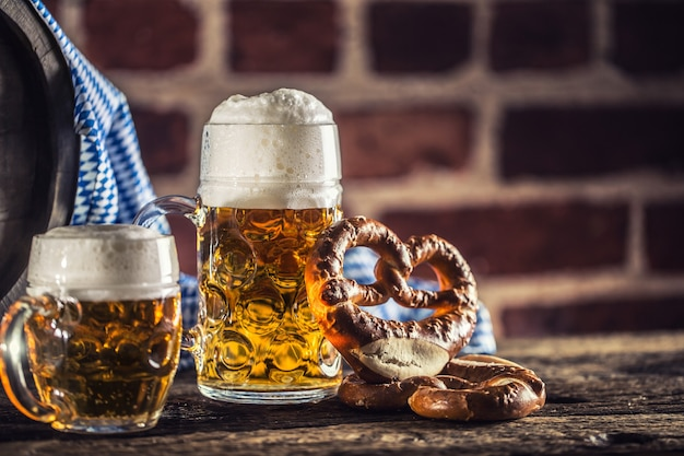 Oktoberfest large and small beer with pretzel wooden barrel and blue tablecloth.