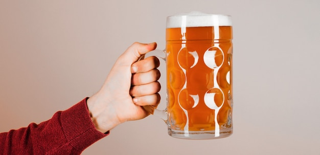 Oktoberfest. man hand with glass of draft beer with foam. fresh cold beer in glass in hand. beer pub.