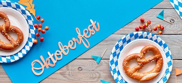 Октоберфест, панорамная квартира на деревянном столе с синей бумагой и кренделями на синих белых бумажных тарелках