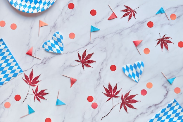 Oktoberfest party background with seasonal decorations, red and orange confetti and maple leaves.