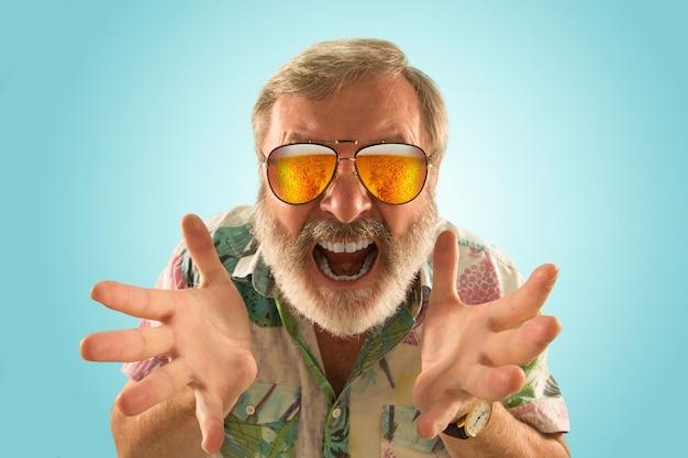 海やアルコールの海を見ながら、軽いビールでいっぱいのサングラスをかけたオクトーバーフェストの年配の男性。顔の表情、びっくり、クレイジーハッピー。お祝い、休日、お祭りのコンセプト。明るい写真。
