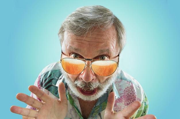 海やアルコールの海を見ながら、軽いビールでいっぱいのサングラスをかけたオクトーバーフェストの年配の男性。顔の表情、びっくり、クレイジーハッピー。お祝い、休日、お祭りのコンセプト。不可能。