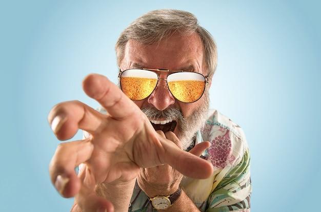 海やアルコールの海を見ながら、軽いビールでいっぱいのサングラスをかけたオクトーバーフェストの年配の男性。顔の表情、びっくり、クレイジーハッピー。お祝い、休日、お祭りのコンセプト。パイントを取ります。