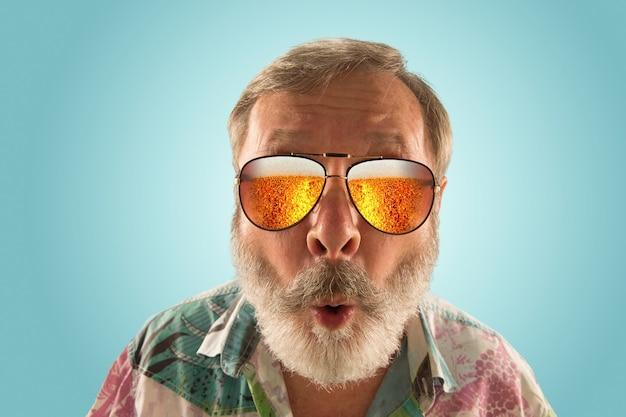 海やアルコールの海を見ながら、軽いビールでいっぱいのサングラスをかけたオクトーバーフェストの年配の男性。顔の表情、びっくり、クレイジーハッピー。お祝い、休日、お祭りのコンセプト。完全に溺れる。